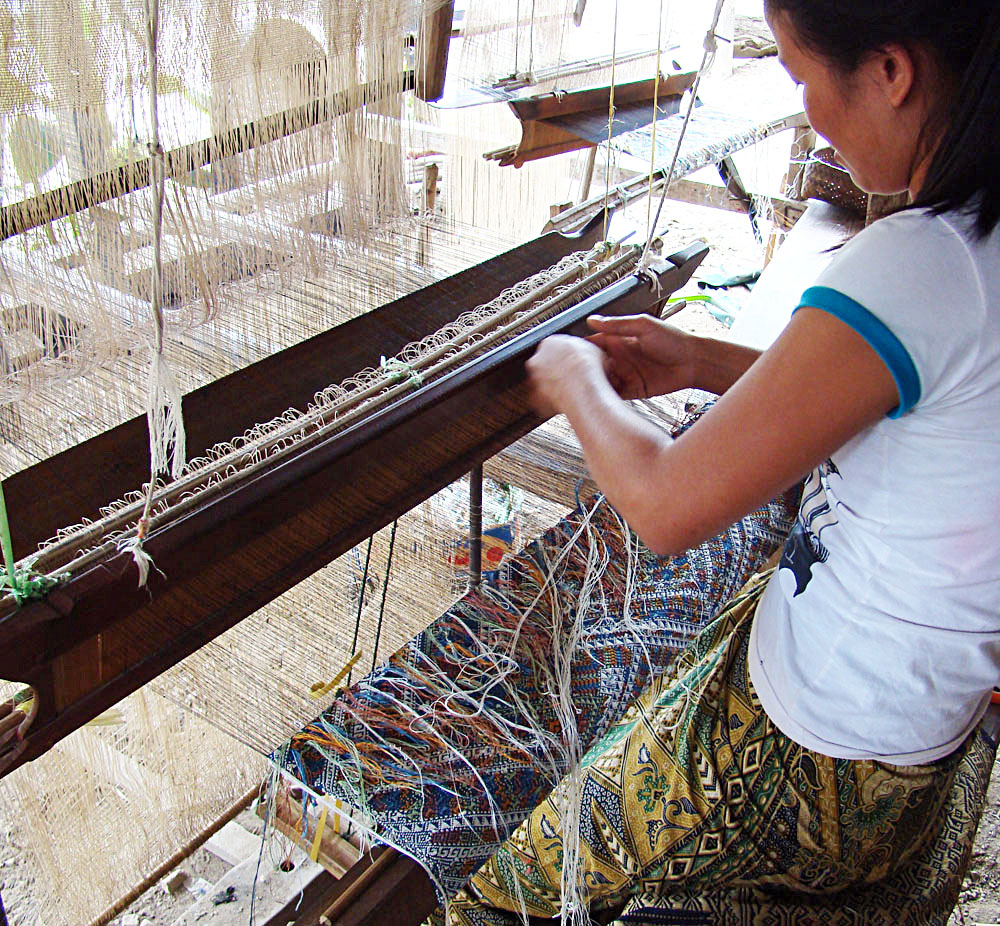 Young weaver picking the supplemental weft color patterns from the back side of the silk cloth.
