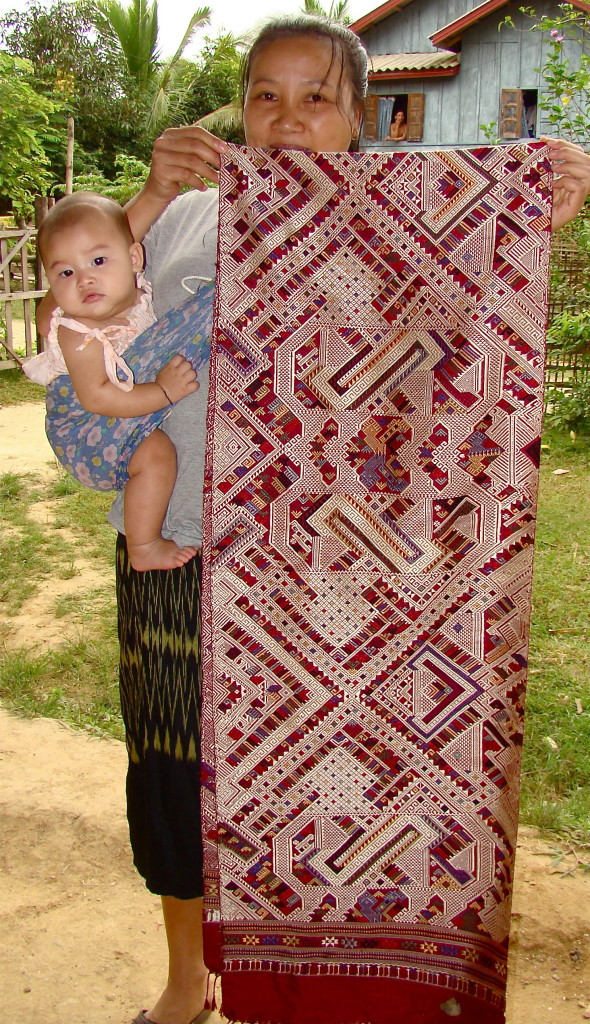 "A woman in Houaphon Province posing with her baby and handwoven ""phaa sabai."""