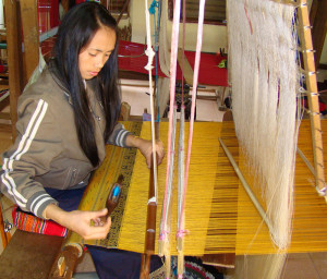 A weaver at work creating another masterpiece.  All of the dyes are made from natural materials, even the bright turquoise on the shuttle she is using for the weft on this golden shawl!