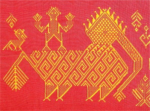 "One of the traditional sets of motifs used by this designer in her shawls.  This shows a ""siho,"" or mythological elephant lion, which represents both political and fierce fighting strength; on its back is an ancestor spirit, who helps guide the shaman to the ancestor world to seek help; a ""hong"" bird, perched to the left, symbolizes male energy. Various flowers, and a spirit tree grow by the siho's trunk."