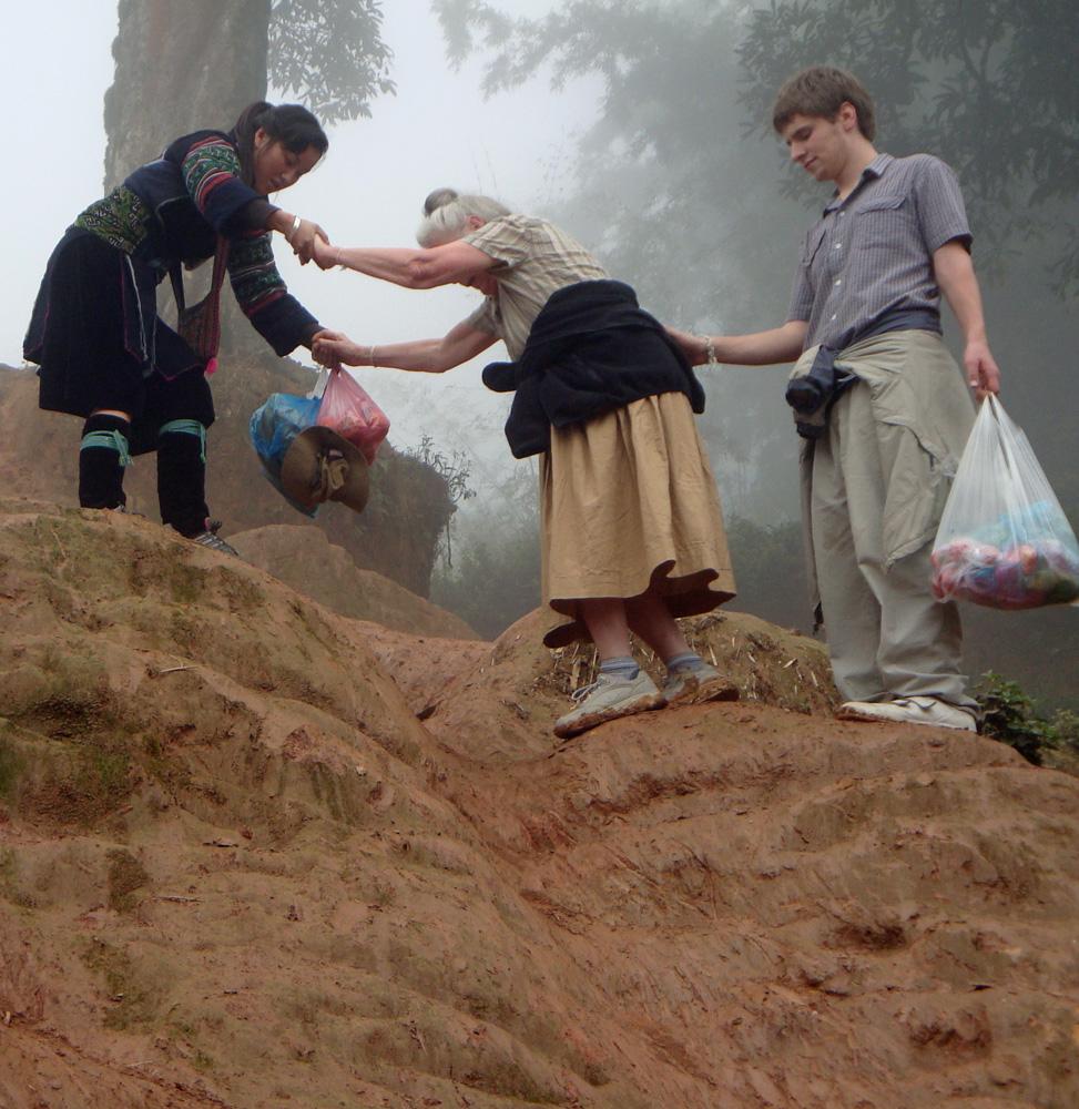 Sho and Ari helping Grandma across a slippery, steep slope.