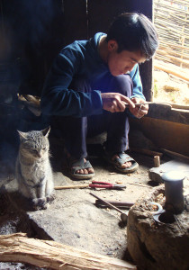 Trang crafting an earring while the cat warms by the fire.