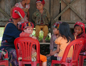 A Red Yao woman and children, with a mix of traditional and western clothing sit on Chinese plastic chairs next to the road.