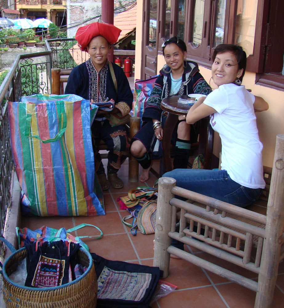 Ta May (in Red Dzao headdress), Tea (in Black Hmong outfit), and Sho (in western garb) on the balcony in front of my room in Sapa. We are labeling items for shipping and customs.