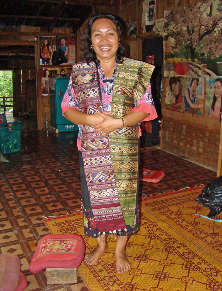 "Our friend Phut (the ""h"" is silent), master-dyer and designer, modeling two of her shoulder cloths in her home. Notice the dichotomy between the turquoise Chinese refrigerator, plastic laundry basket, vinyl floor, and posters, and the traditional wooden stool with the hand- woven pillows and door curtain. This is one of the finest homes in Xam Tai."