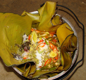 The frog dish in a banana leaf in a pot, ready to cook - you can see the brown frog leg on the left side.