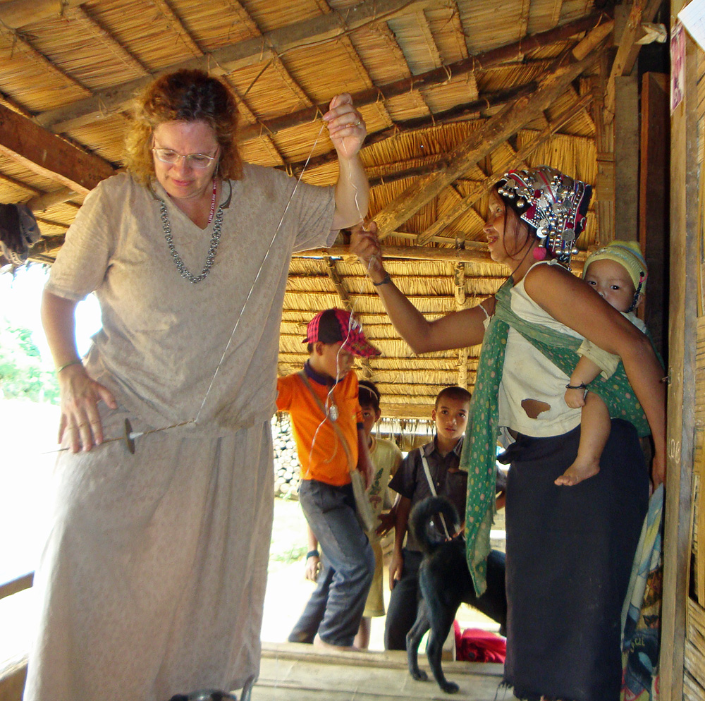 """Maren learning from an Akha expert how to use a drop spindle to make recycled plastic """"yarn""""."""
