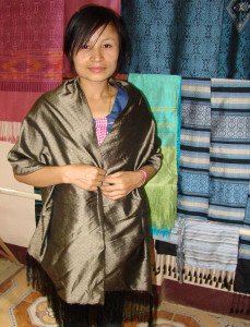 One of the young weavers modeling a shawl she just wove (note untwisted fringes) standing in front of finished shawls from the weaving works.