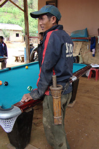 A young Lao man in western clothing playing pool with his friends while still wearing his hand-forged machete with a wooden hilt and handwoven rattan scabbard.