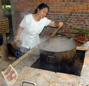 Vandara stirring a dye-pot full of annatto dye – see the seeds in the bamboo tray on the bottom left.