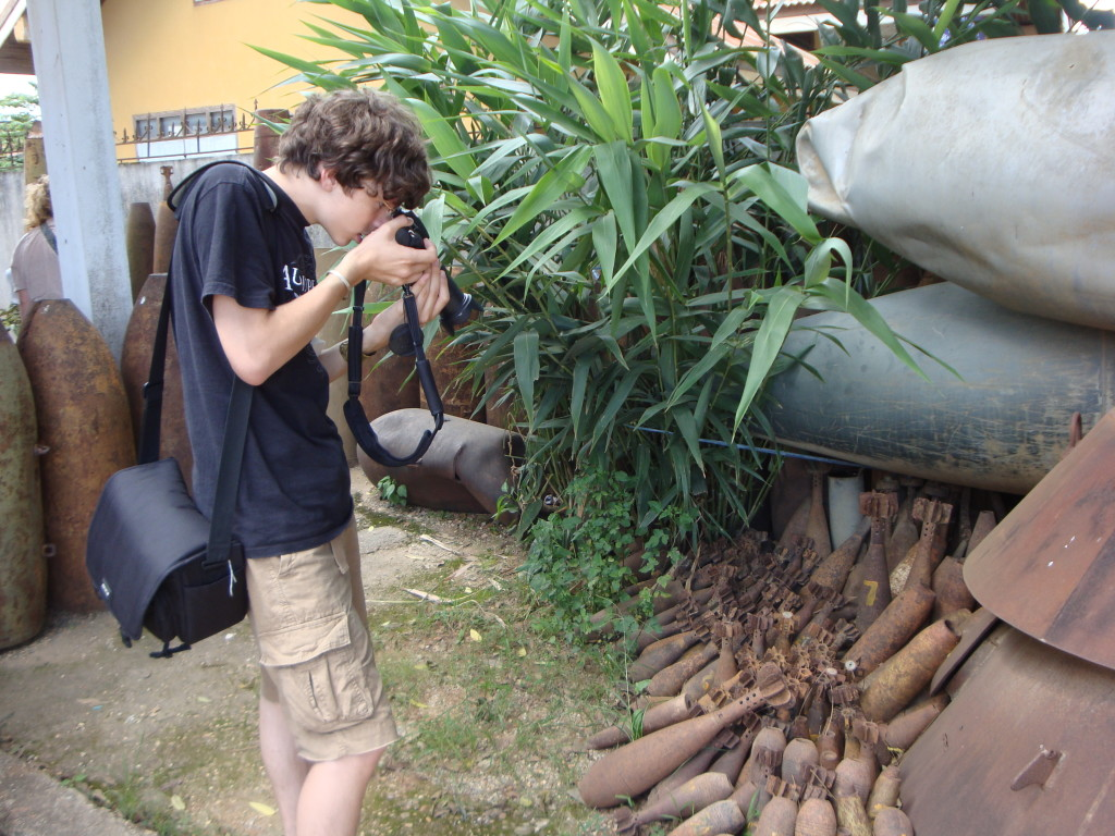 Zall at work photographing defused mortar shells and other bomb scrap.