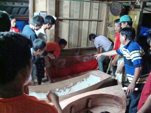 The body being lifted into place in the cotton and fabric lined coffin.