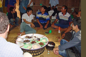 Meal of water buffalo, pork, and rice with Mr. Champa and village elders.