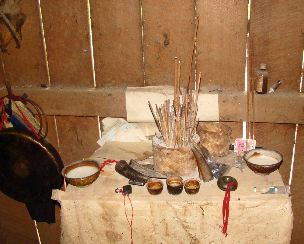 A Hmong shaman's altar with bowls, incense, gong, sword, offering cups, and bronze bells.