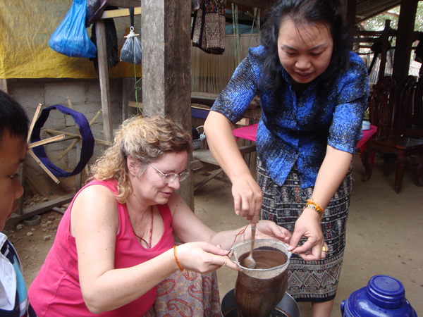 Maren hold the coffee filter while Phut stirs. Traditional Lao coffee, which is not readly available in the north, is sweet and thick, very different from our breakfast java.