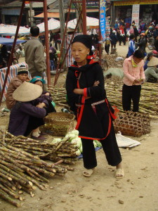 Red Dzao woman in front of sugar cane and chicken (in bamboo basket) seller.