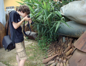 "Zall on the job, photographing bombs, mortars, and fuel tanks from the ""American War""."