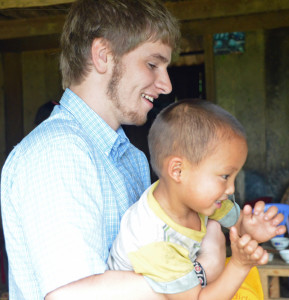 Ari plays with a child in Vietnam.