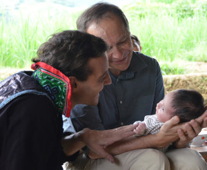 Antoine (in his  Black Hmong clothing) and his dad admire beautiful baby Alice.