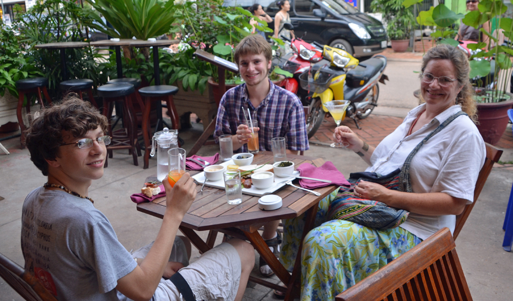 Zall and Maren enjoy visiting with Ari (center) over dinner during his internship in Vientiane.