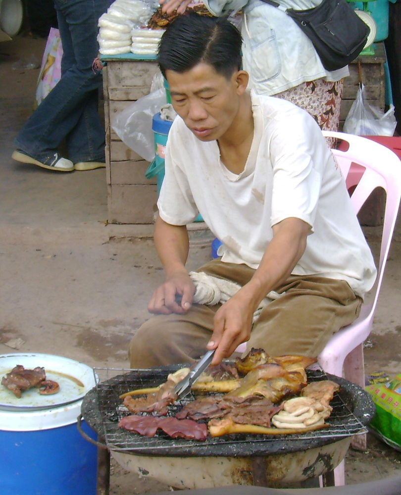 A Lao man in the market grilling a pig face, intestines, liver, tail, and other offal.