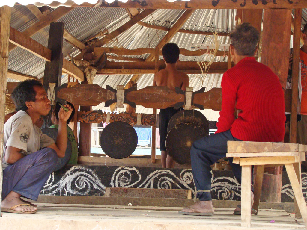 Men in a Katu community house during their New Year's celebration in Laos – see the gongs?