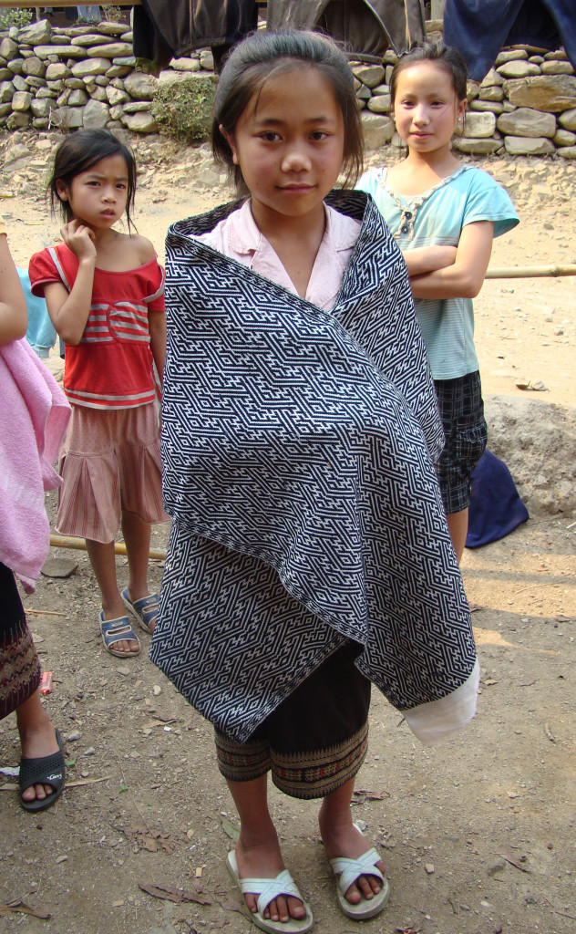 A young girl in Muang Vaen displaying the cotton shawl she wove.