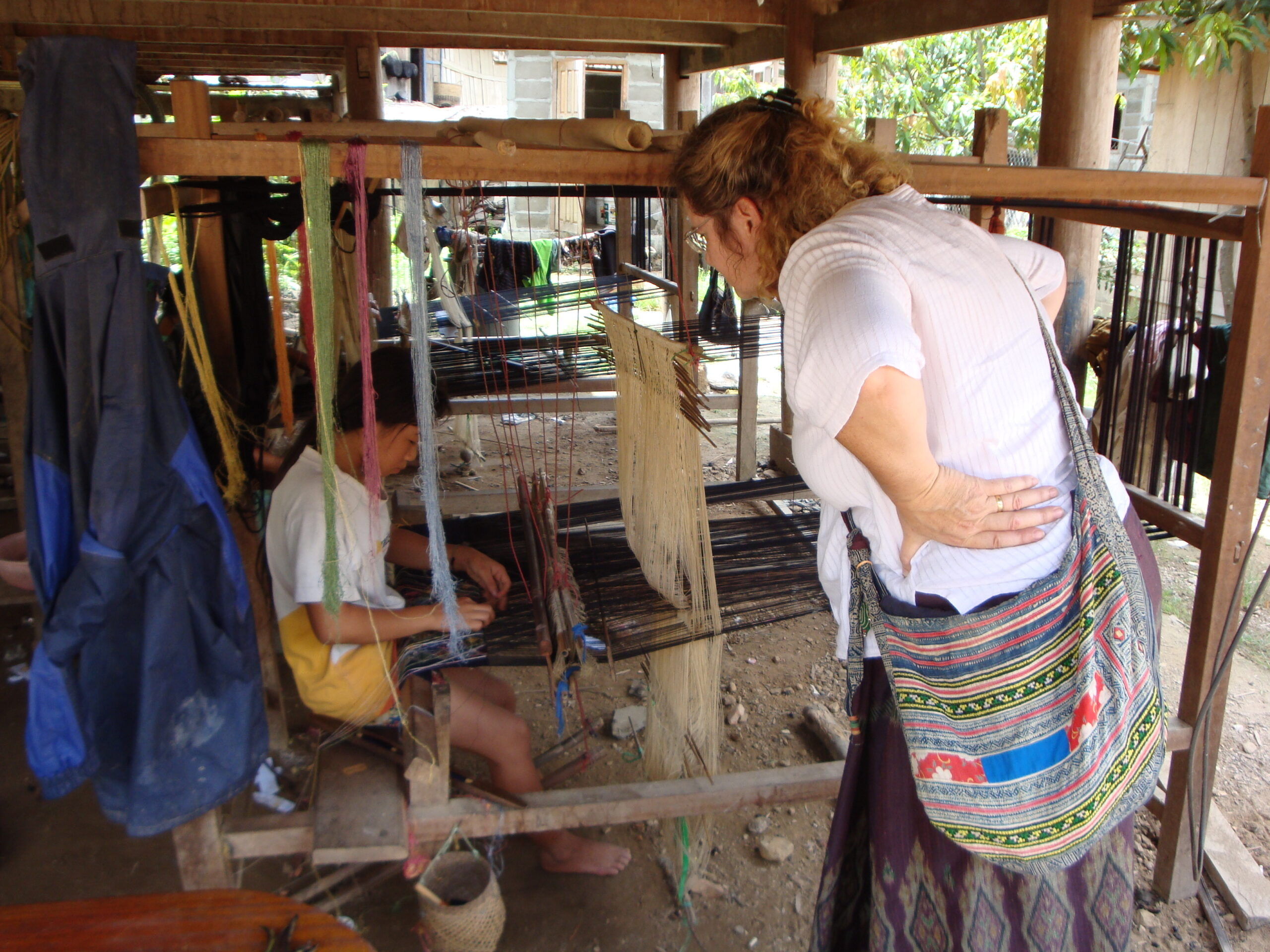 Maren leans in to watch; weaving can be mesmerizing!