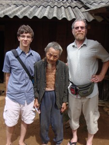 Zall, the very elderly Hmong blacksmith, and Josh in 2014.  The gentleman is holding a picture of himself with our boys from many years ago.