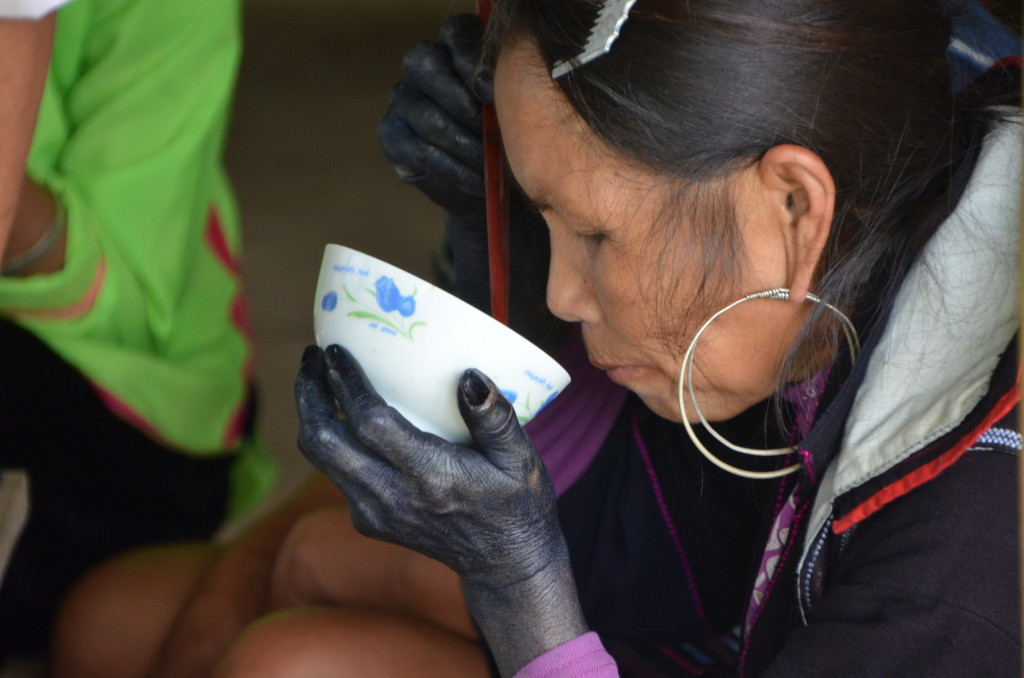 "A ""Black Hmong"" woman catches a meal in between shifts of dyeing local hemp with indigo."