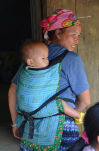"A woman shows off her baby - and beautifully embroidered baby-carrier made of local hemp and cotton. The textiles coloring and patterns ndicate the woman's ethnicity is of the ""Blue kong"" people."