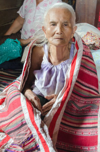 The elderly woman modeling the mosquito-net border which she wove some 60 years ago.