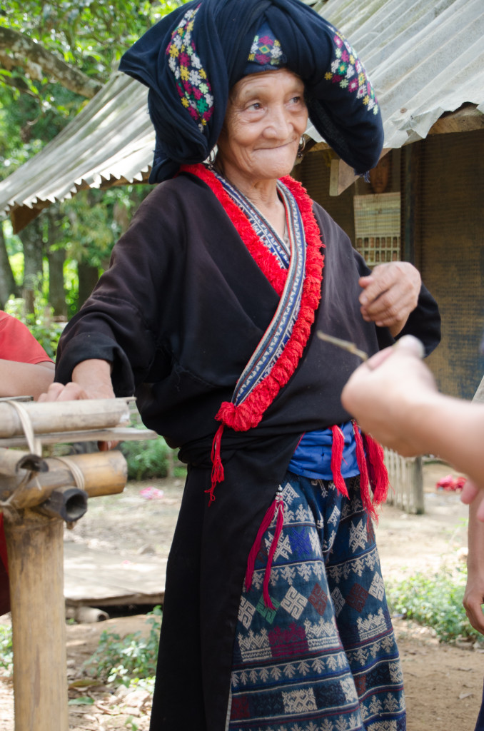 An Red Dzao elder models an outfit she recently made. She happily sold it to us.