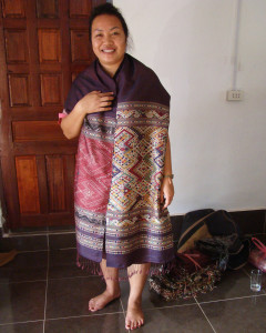 "Phout models one of her ""man-woman"" healing cloths. Phout is known for her rich purples and reds."