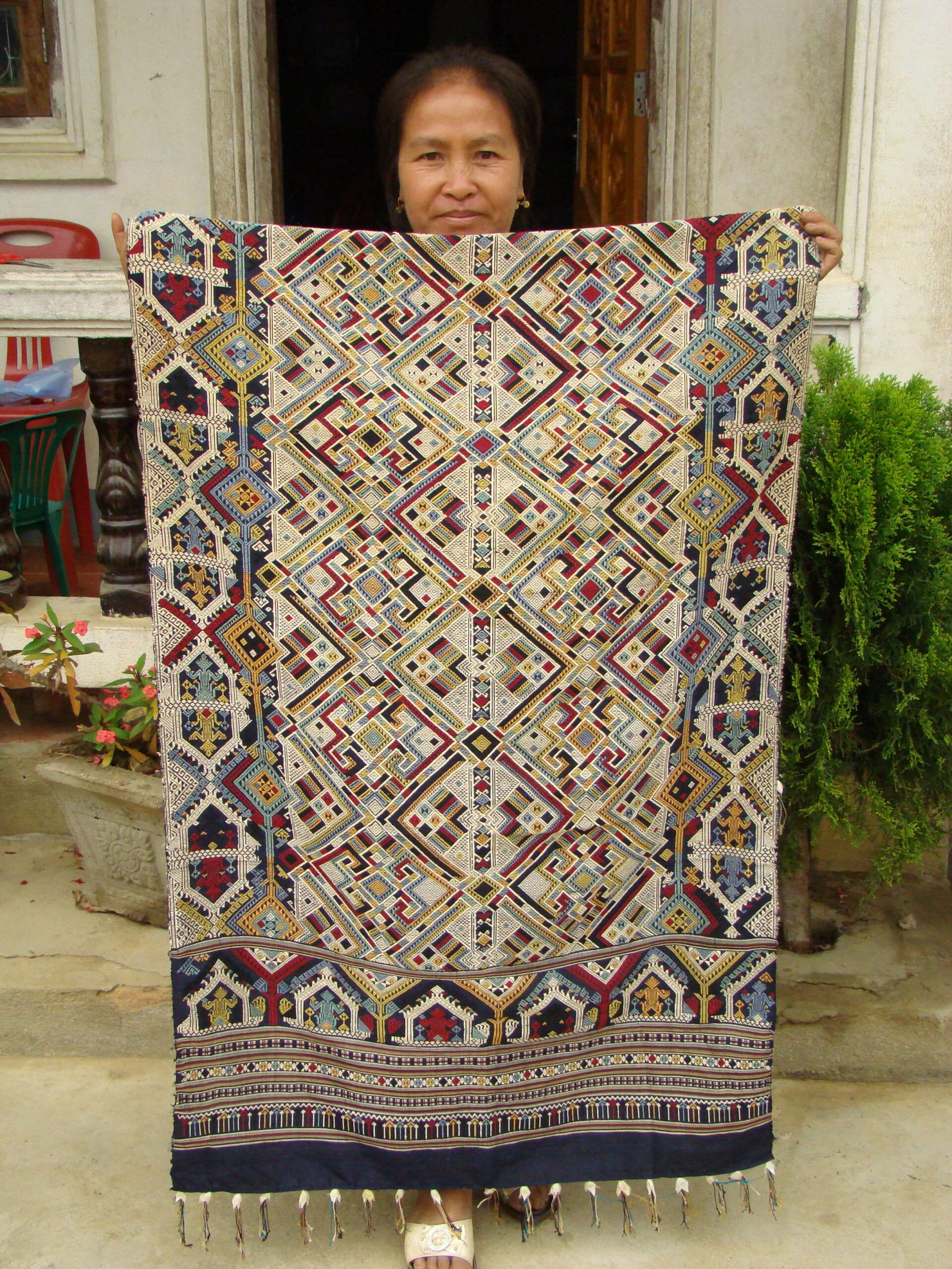 Lun displays one of her masterpieces, a ceremonial wedding blanket.