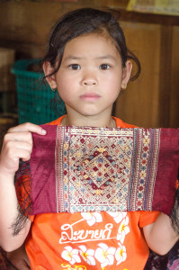 "An 8-year old silk weaver with a ""sample-sized"" silk, affectionately called a ""love token."""
