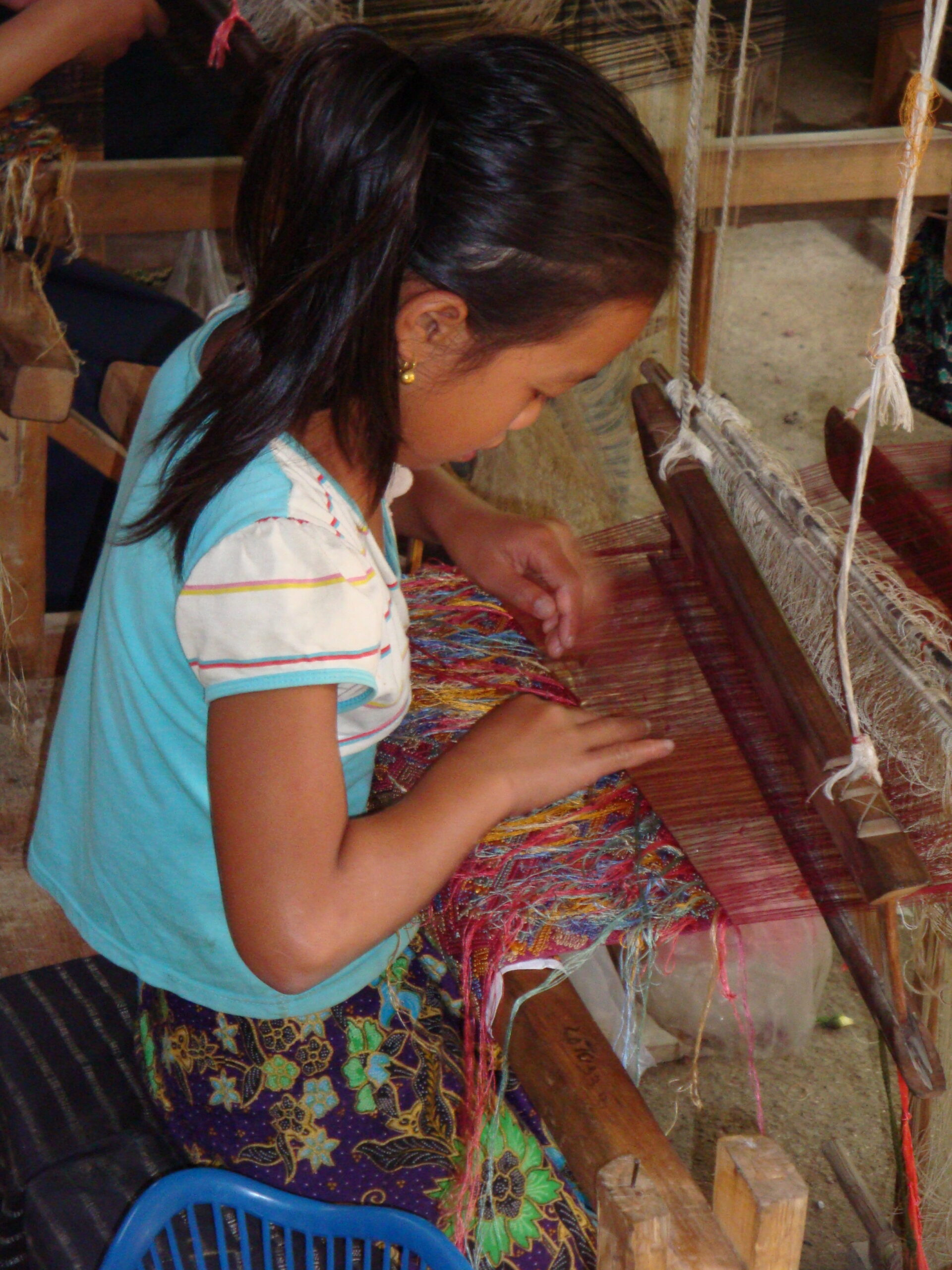 A 13-year-old weaver works on a silk healing cloth.