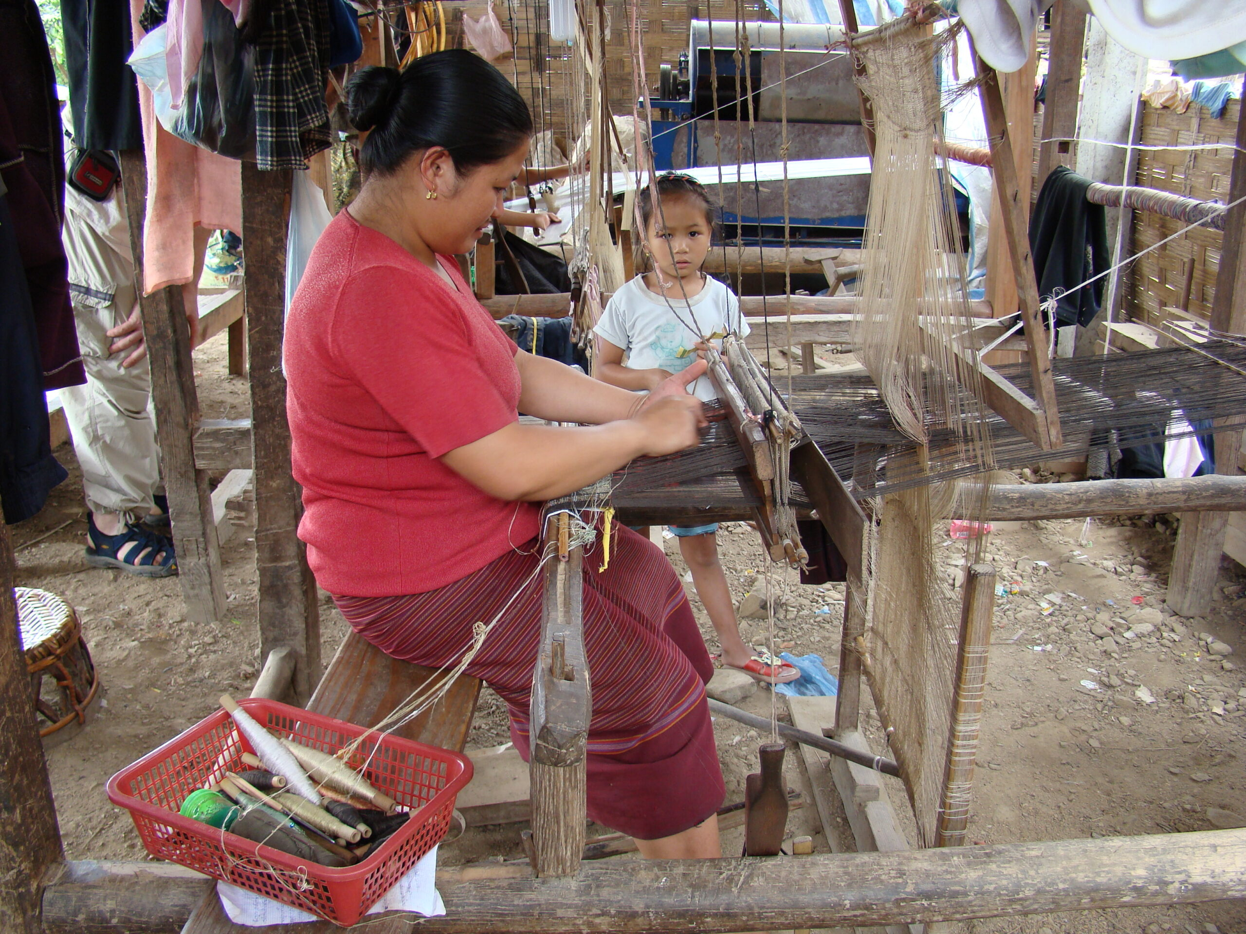 A weaver works at her village-made loom.