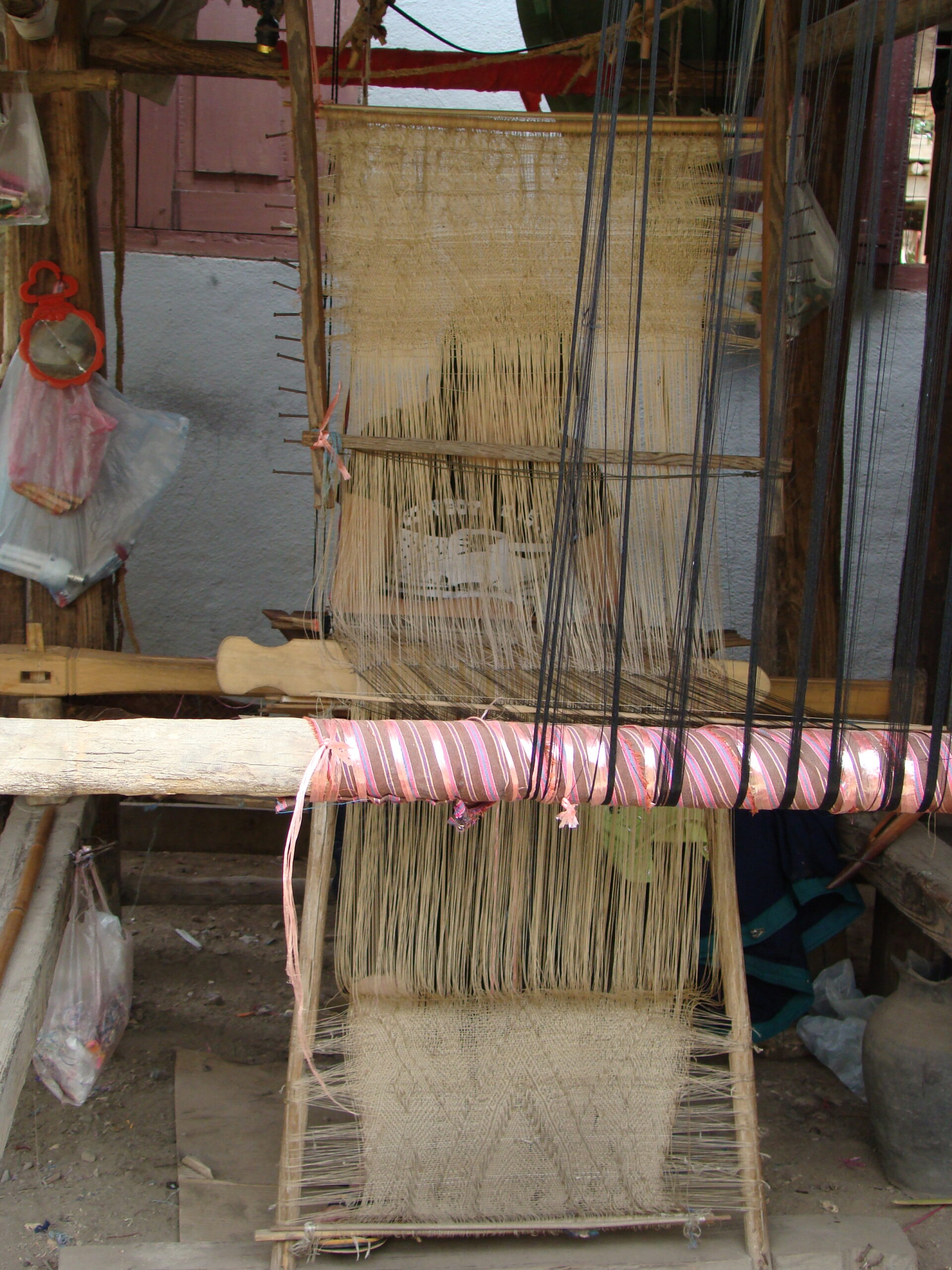 The design of the template-pattern can be clearly seen on this loom.  After each horizontal memory-thread, which represents a line of pattern in the weft, is used, it is moved from the template's top to the bottom; later, the memory threads will be moved from bottom to top, creating the traditional mirror-image motifs in the design-work.