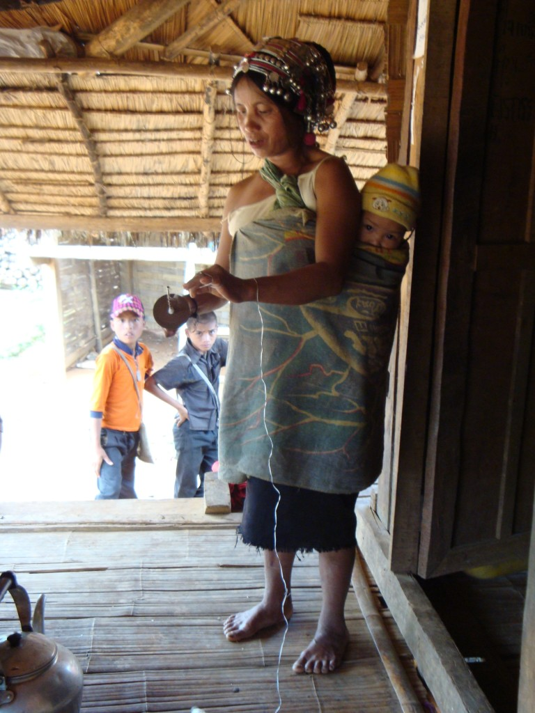 The Akha-Puli woman winds her spindle