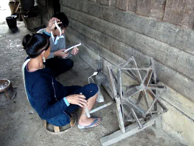 A Lanten woman spins cotton.
