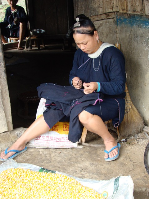 A Lanten woman sews the edging onto her indigo-dyed handspun cotton outfit.