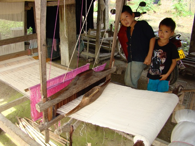 Hand-spun cotton being handwoven. Look at the patina on that huge shuttle!