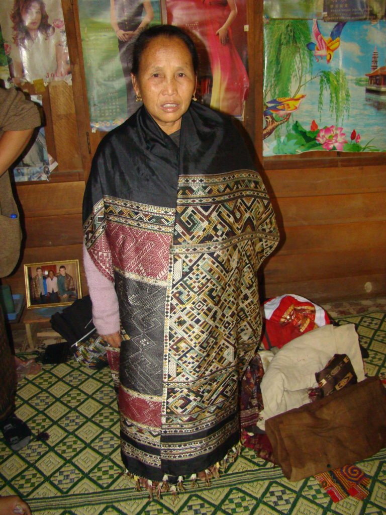 "Phout's aunt, Sukkhavit, dons a shaman's traditional healing cloth; this one is not of the ""man-woman"" style."