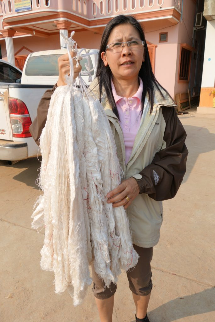 Malaithong with an armload of freshly processed silk.  The silk worms are raised locally.