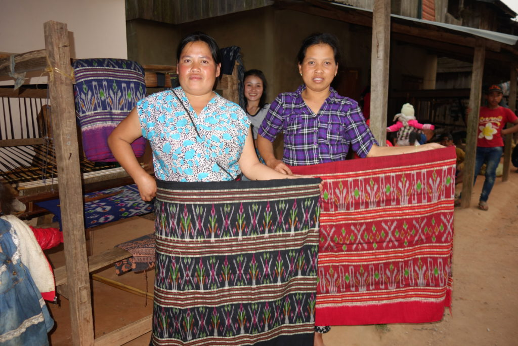 Two weavers display their recently woven silk sinh (skirts).