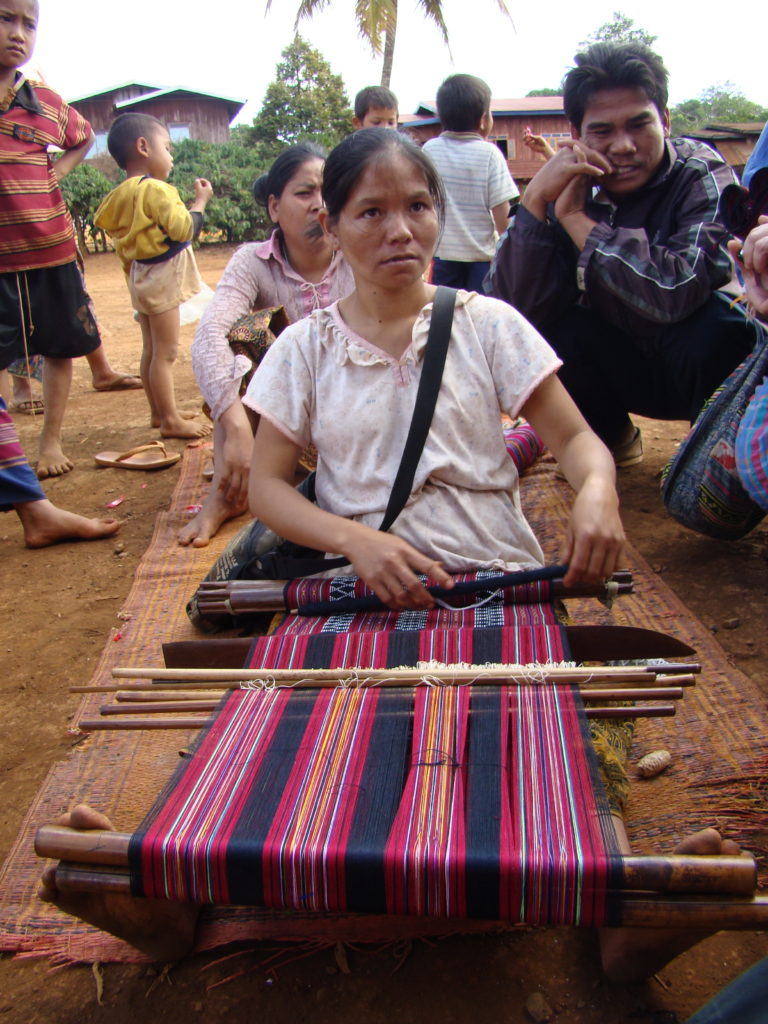 A Katu woman in Attapeu Province weaves a traditional cloth on her backstrap loom. White glass beads are being woven onto the textile's weft threads. The yarns are chemical-dyed polycotton. Photo by Above the Fray.
