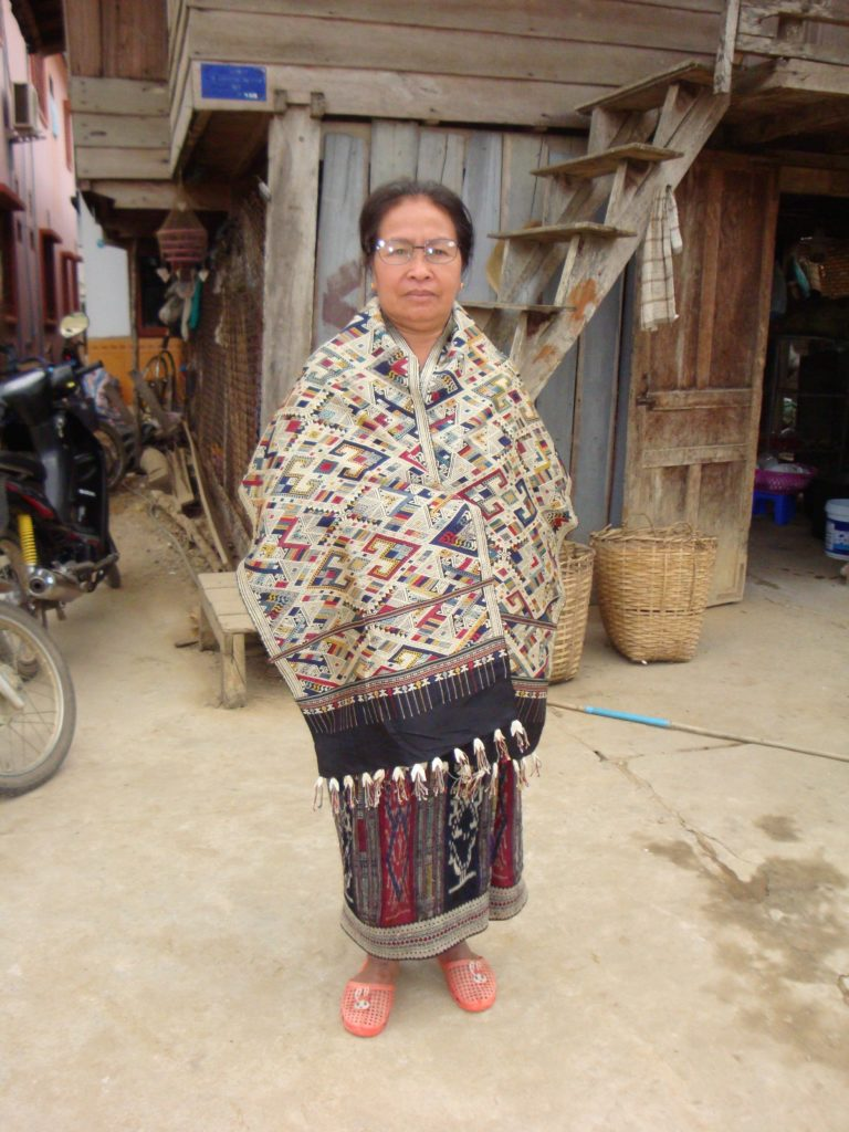 Lun, a master dyer and weaver from Houaphan Province, Laos, dons her silk phaa phi mon, or Shaman's shawl. The silk is locally-raised, hand-reeled, naturally-dyed, and handwoven on a floor loom. Note the flower-like tassels! Photo by Above the Fray.