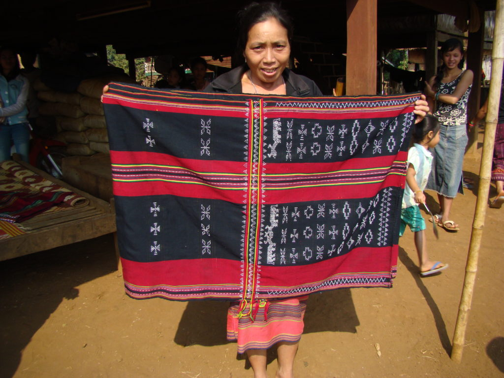 A Katu weaver holds up a stunning man's ceremonial shoulder cloth that she recently wove. Photo by Above the Fray.